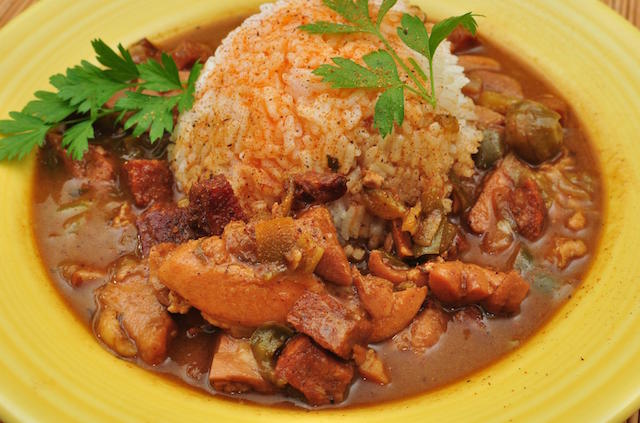 A yellow dish with chicken gumbo mixed with rice and a cajun sauce.